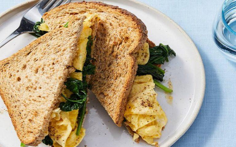 Gezonde sandwich met roerei en gebakken spinazie